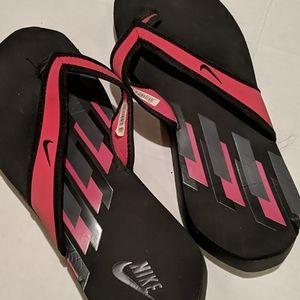 Hot pink and black Nike flip flops